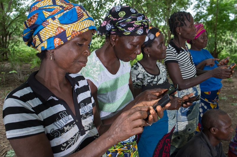 Women use their mobile phones to receive weather data via text messages. Photo: Klaus Wohlmann, GIZ